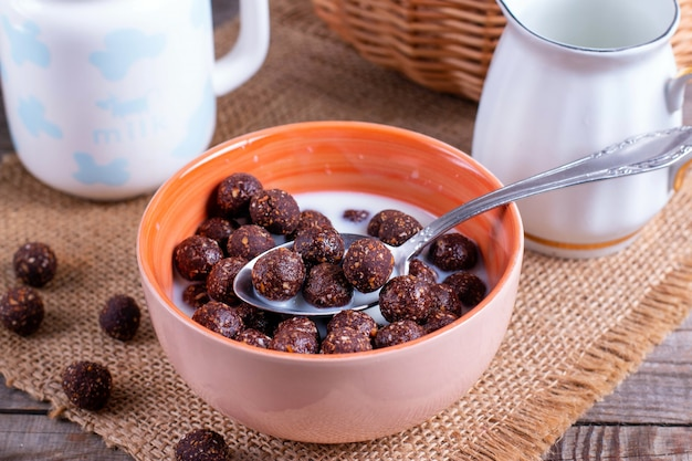 Bolas de chocolate em uma tigela com leite. café da manhã saudável e conceito de dieta