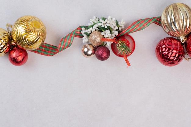 Bolas de decoração de natal com banda na mesa branca.