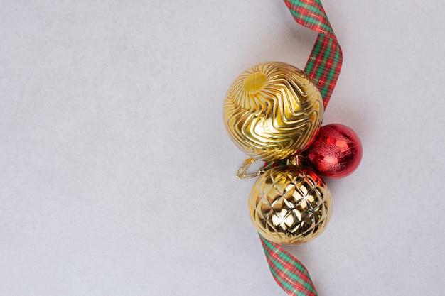 Bolas de decoração de natal com banda na superfície branca