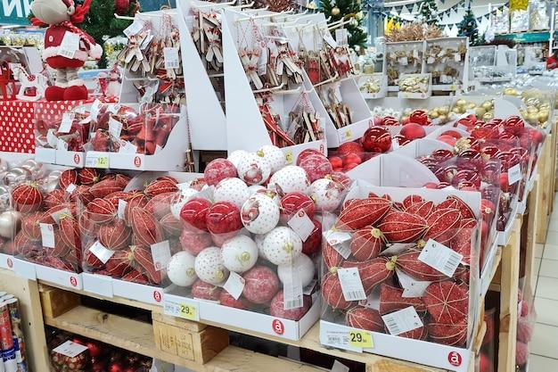 Bolas de decoração de natal vermelhas e brancas são vendidas no balcão de uma loja