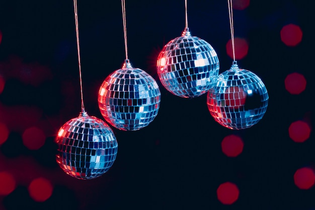 Bolas de discoteca brilhantes penduradas no ar contra preto