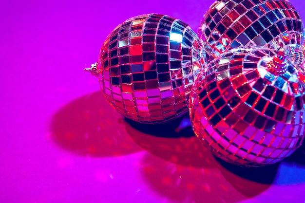 Bolas de discoteca pequenas brilhantes brilhando em uma bela luz roxa, conceito de festa de discoteca
