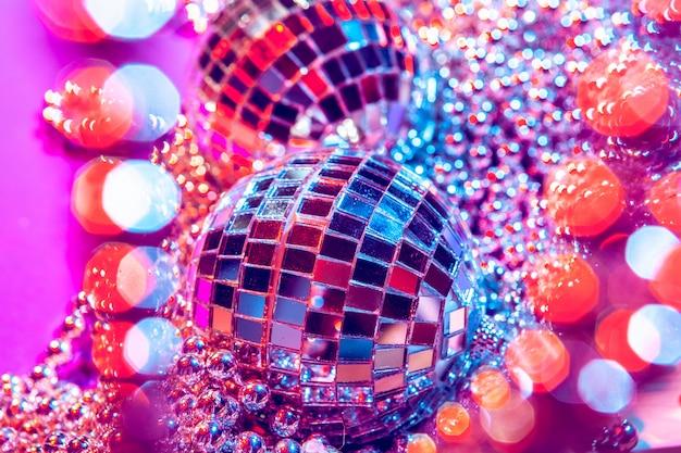Bolas de discoteca pequenas brilhantes brilhando em uma bela luz roxa. conceito de festa discoteca