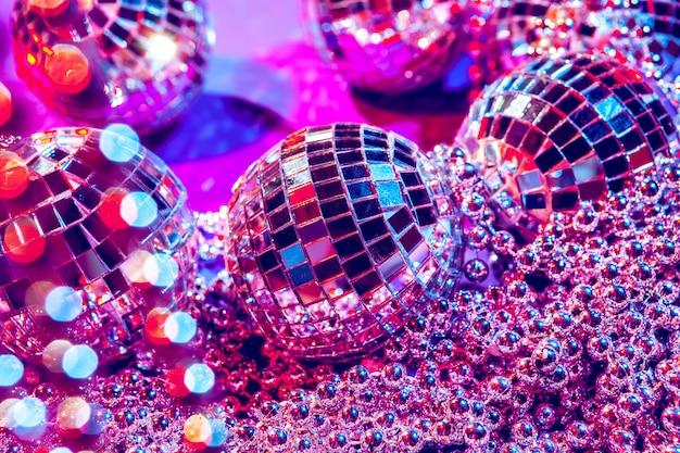 Bolas de discoteca pequenas brilhantes brilhando em uma bela luz roxa. festa discoteca