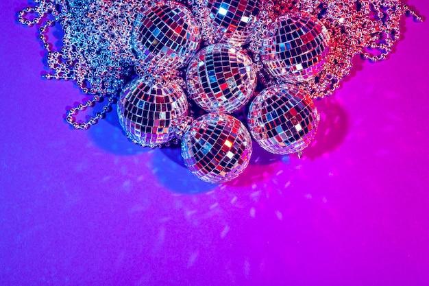 Bolas de discoteca pequenas brilhantes brilhando em uma bela luz roxa.