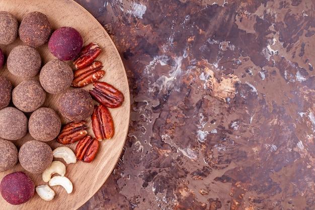 Bolas de energia caseira de cacau vegano cru na placa de madeira na mesa de mármore marrom