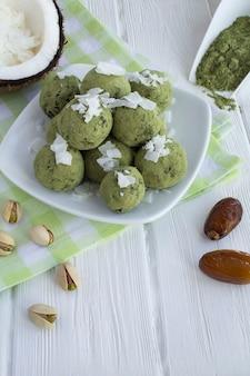 Bolas de energia com pó matcha, pistache, tâmaras e lascas de coco no prato branco sobre a mesa de madeira branca.