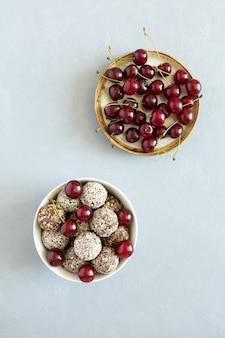 Bolas de energia crua caseiras de doces veganos com bagas de cereja planas colocadas em pratos sobre fundo cinza de concreto