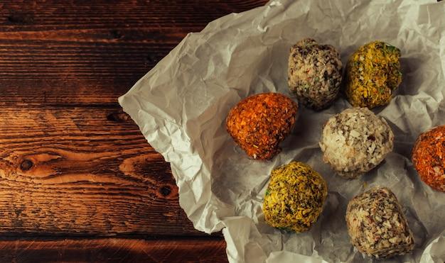 Bolas de energia crua saudável com coco em pergaminho em uma mesa de madeira.