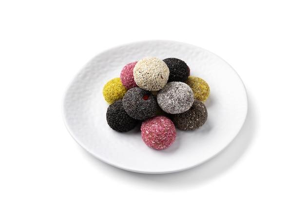 Bolas de energia de doces vegan coloridos em um prato sobre uma mesa branca.