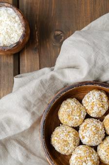 Bolas de energia doce caseiras saudáveis de frutas secas e nozes em coco.