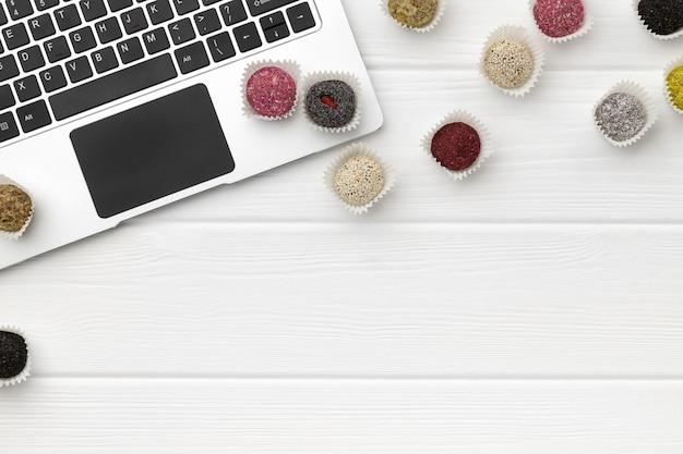 Bolas de energia doces veganos perto do laptop na mesa de madeira branca