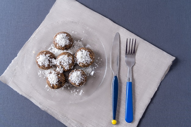 Bolas de energia orgânica saudável, feitas com tâmaras, ameixas, passas, amendoim, em um prato