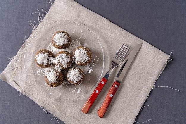 Bolas de energia orgânicas saudáveis feitas com tâmaras, ameixas, passas, amendoim, com raspas de coco