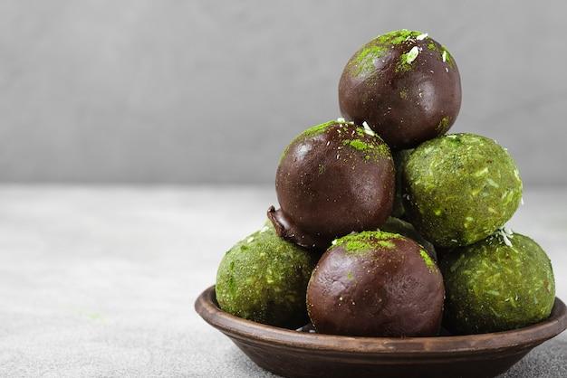 Bolas de energia. sobremesa vegan crua matcha saudável ou bolas de felicidade em cobertura de chocolate na superfície de concreto cinza. fechar-se