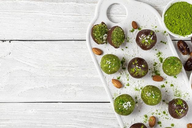 Bolas de êxtase de coco matcha ou bolas de energia. doces vegetarianos vegan sem açúcar em fundo branco de madeira. vista do topo. postura plana