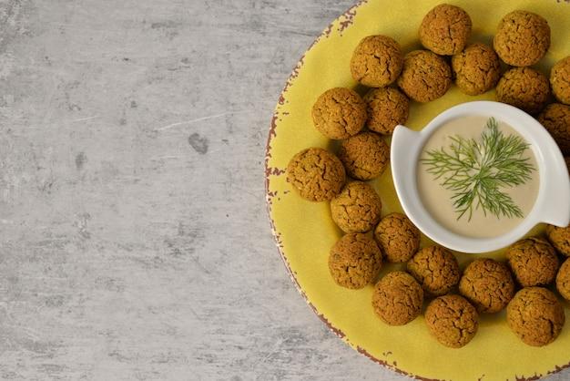 Bolas de falafel de grão de bico cozido na placa amarela na comida cinza, saudável e vegan com tahine profundo, tradicional mediterrâneo, vista superior, plana leigos com espaço de cópia