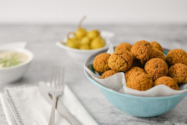 Bolas de falafel de grão de bico cozido na placa azul na comida cinza, saudável e vegan com tahine pimenta profunda e quente, mediterrâneo tradicional, vista superior, plana leigos com espaço de cópia