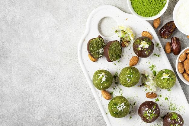Bolas de felicidade matcha ou bolas de energia em cobertura de chocolate. lanches saudáveis veganos vegetarianos em fundo cinza com flores. vista do topo. postura plana