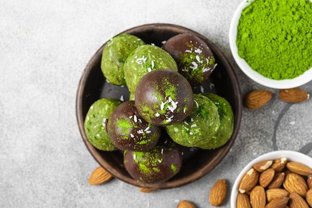 Bolas de felicidade matcha ou bolas de energia em cobertura de chocolate. lanches saudáveis veganos vegetarianos na superfície cinza. vista do topo. postura plana