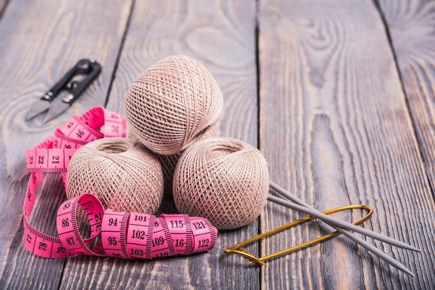Bolas de fio, agulhas de tricô e fita métrica em um fundo de madeira.