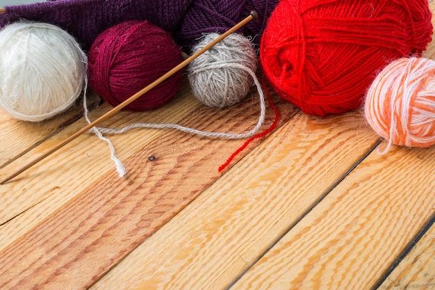 Bolas de fio colorido em uma mesa de madeira