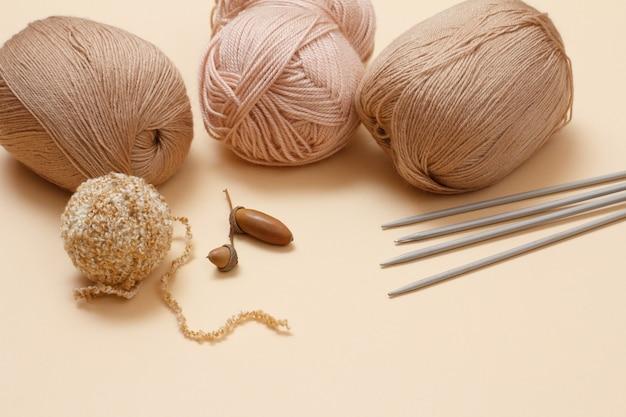 Bolas de fio de tricô, agulhas de tricô de metal e bolota em um fundo bege. conceito de tricô.
