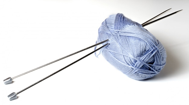 Bolas de fios azuis e agulhas de tricô.