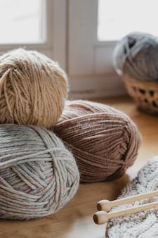 Bolas de fios de cores terrosas e cobertor