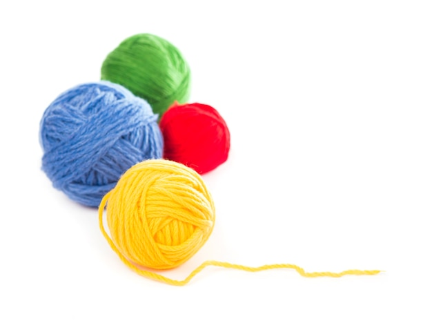 Bolas de fios de lã azuis, vermelhos e amarelos sobre fundo branco