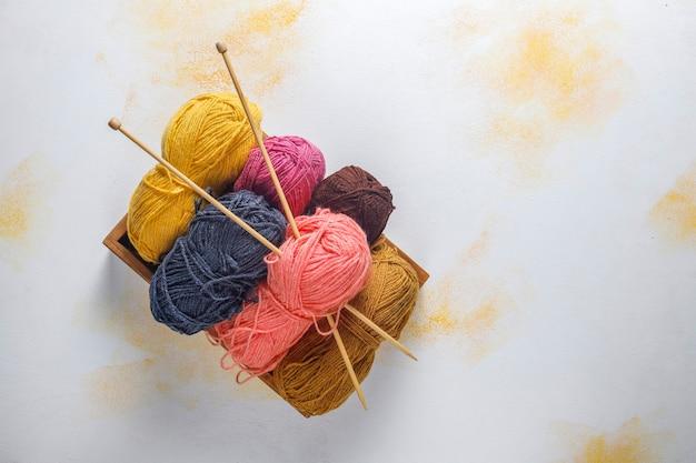 Bolas de fios em cores diferentes com agulhas de tricô.