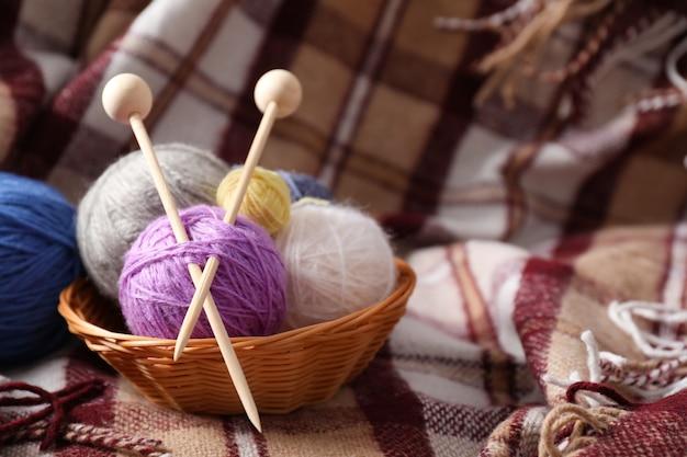 Bolas de fios multicoloridos com agulhas de tricô em uma cesta de vime no fundo de uma manta.