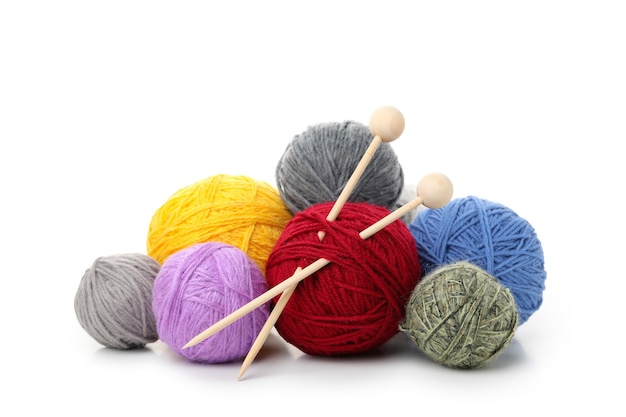 Bolas de fios multicoloridos com agulhas de tricô, isoladas no fundo branco.