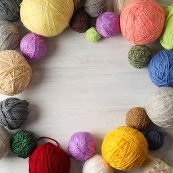 Bolas de fios multicoloridos sobre fundo branco de madeira.
