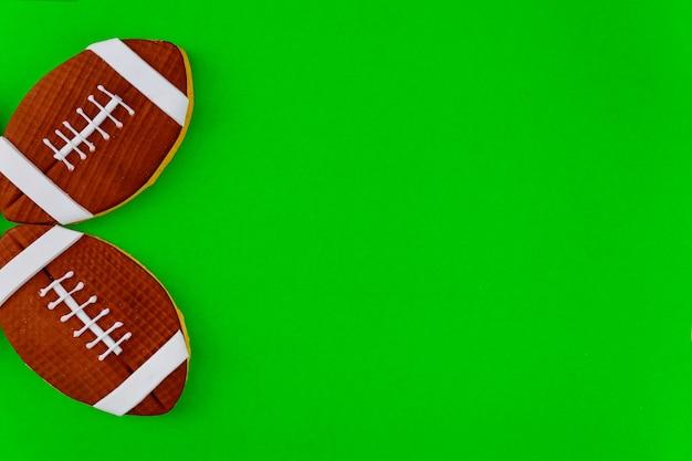 Bolas de futebol americano isoladas sobre fundo verde. vista do topo.