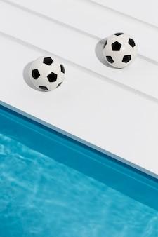 Bolas de futebol ao lado da piscina