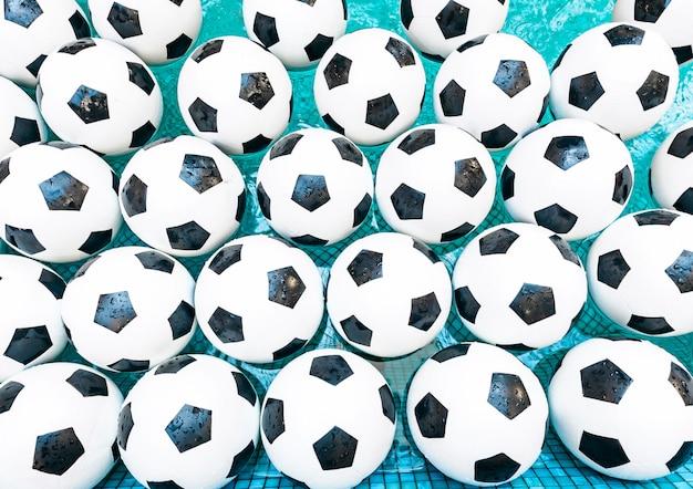 Bolas de futebol em uma água