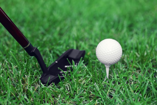 Bolas de golfe e driver na grama verde