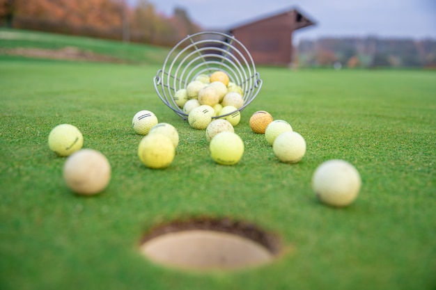 Bolas de golfe e paus no campo de golfe verde