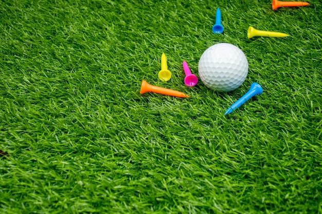 Bolas de golfe e tees estão na grama verde.