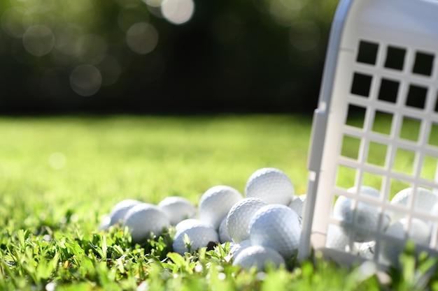 Bolas de golfe em uma cesta na grama verde para praticar