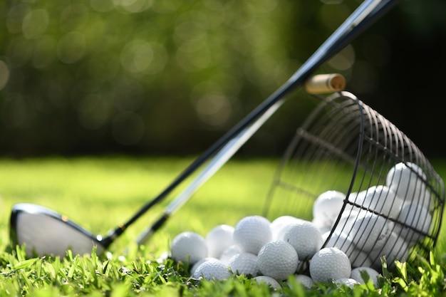 Bolas de golfe na cesta e tacos de golfe na grama verde para praticar