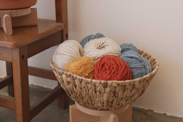 Bolas de lã coloridas na cesta na cadeira