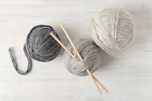 Bolas de lã com agulhas de tricô em fundo branco de madeira.