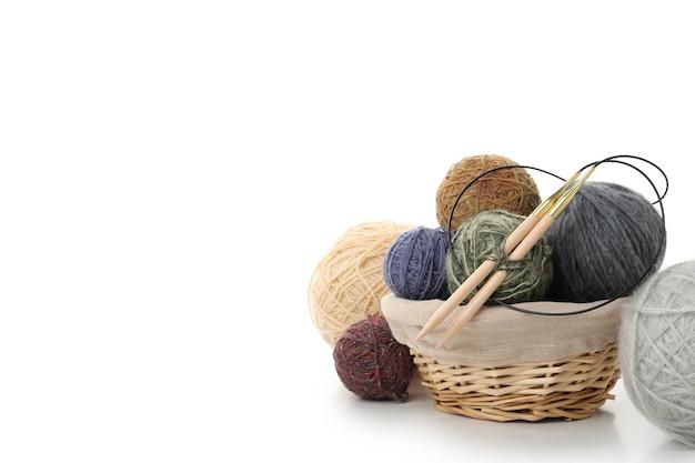 Bolas de lã com agulhas de tricô na cesta isolada no fundo branco.