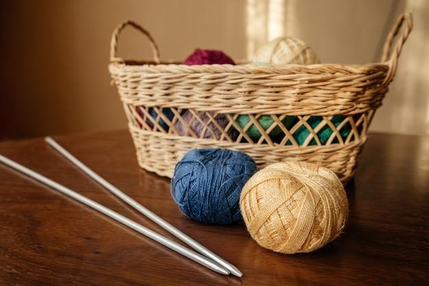 Bolas de lã deite na mesa de madeira perto com cesta de vime com agulhas de tricô