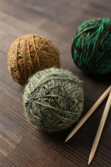 Bolas de lã multi coloridas com agulhas de tricô em um fundo de madeira.