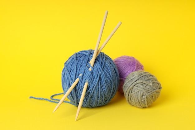 Bolas de lã multicoloridas com agulhas de tricô em fundo amarelo.