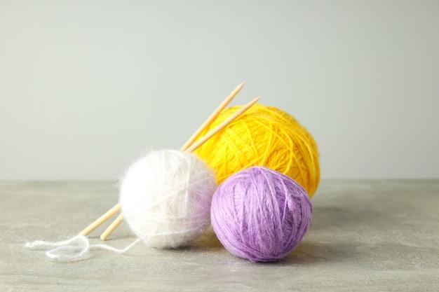 Bolas de lã multicoloridas com agulhas de tricô em fundo cinza claro.