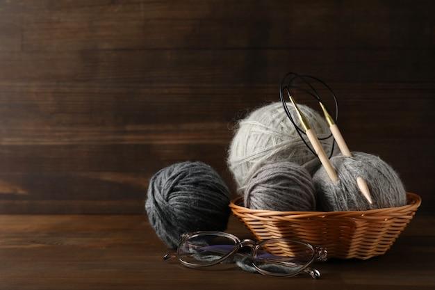 Bolas de lã multicoloridas com agulhas de tricô em uma cesta de vime em um fundo de madeira.